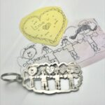 Detailed family drawing by kids transformed by hand into a key chain in durable titanium