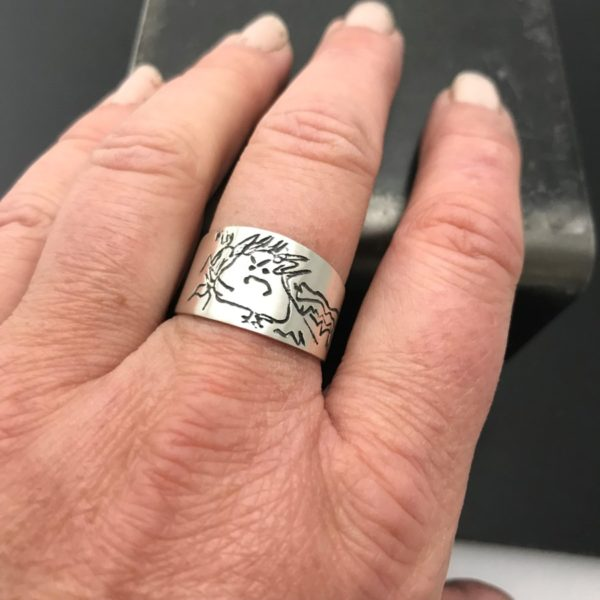 drawing on ring, wide band on finger with self portrait
