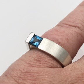 Square blue topaz in modern simple design shown on finger