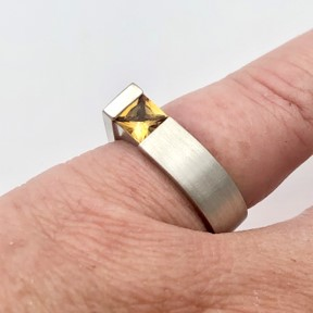 Square cut yellow topaz in contemporary ring design seen on pinky finger