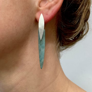 Earrings on ear with green stone