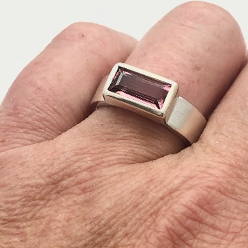 Pink tourmaline bezel across ring, shown on the finger
