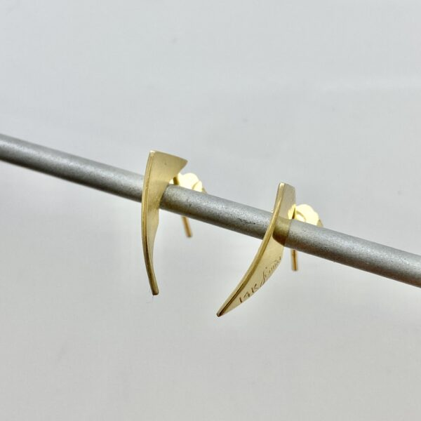Gold cutting edge earring a slice through the earlobe